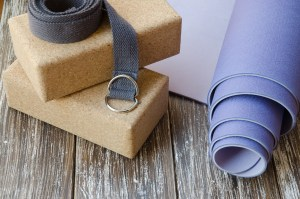 Image shows two cork yoga blocks, a yoga strap, and a rolled up yoga mat