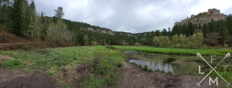 An image taken from a river side. The river sits in a bit of a marsh.  The river proceeds to cut a valley between two ridges. on the right a high rocky point. the background is full of an assortment of trees.
