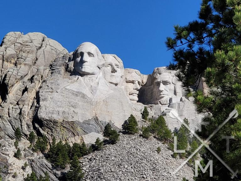 wide shot of the 4 president faces carved into Mount Rushmore.  There is a small row of pine trees lining the base of the mountain.