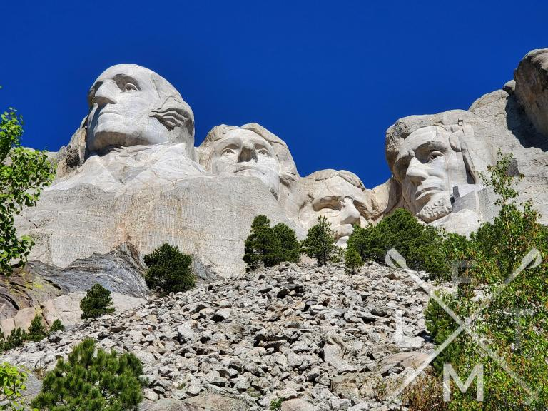 A view of the 4 presidents of Mount Rushmore from closer up and underneath.  The foreground is of a rocky hill topped with trees that leads to carvings.