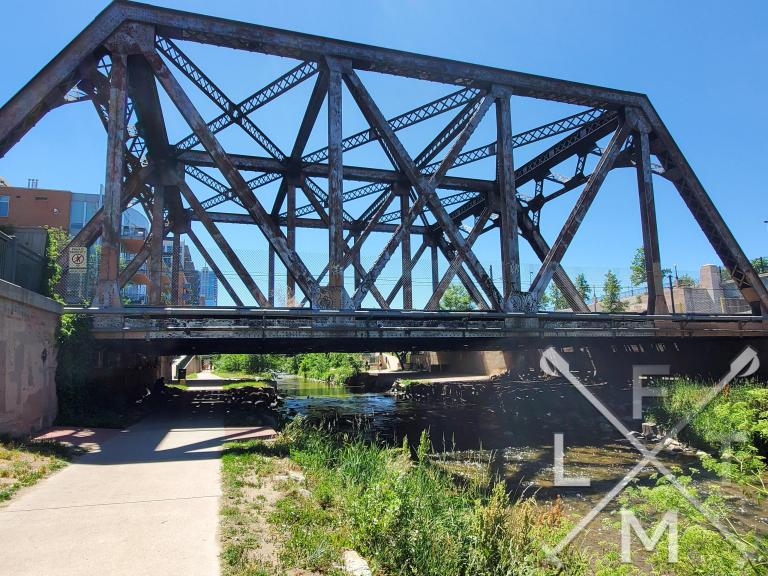 An old iron railroad bridge that stretches across the path and the Cherry Creek.  The iron on the bridge is rusting and petina-ed