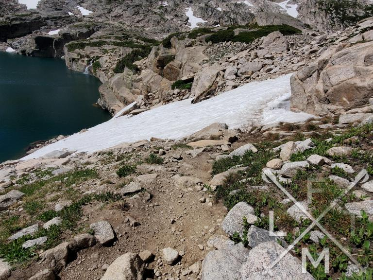 The path across the snow with a sheer drop to the lake below.