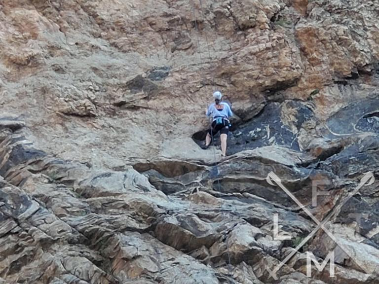 A climber about half way up the cliff side looking for their next move.