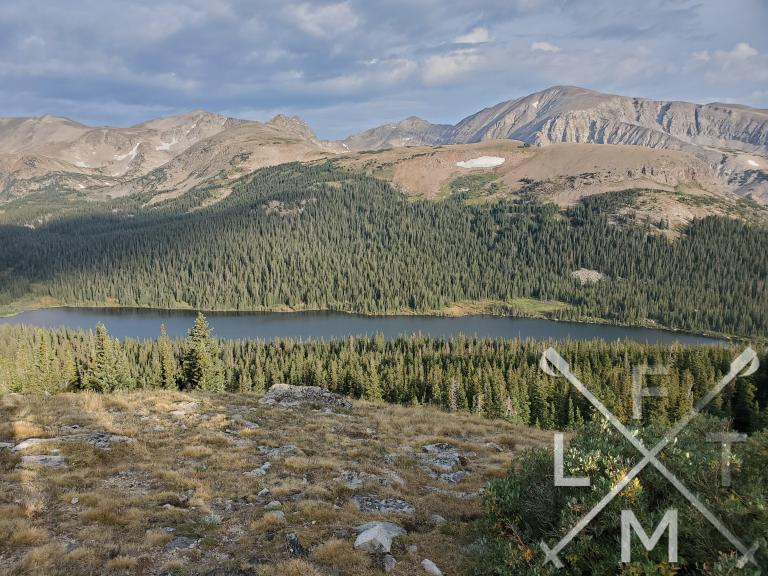 A view of Long Lake  from about halfway up the Niwot Ridge trail.  There are pine trees surrounding the lake with the lake in the center and mountain peaks in the background.