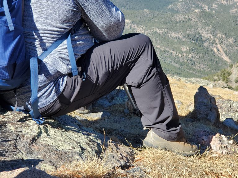 Me wearing the Traverse pants sitting on a cliffside showing off the flexibility in the pants.