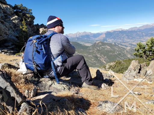 The Closet stage of the Hiking Seasons as depicted by the Fatman hiking in the mountains with an huge backpack overstuffed with clothing.