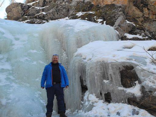 The Frozen stage of theHiking Seasons as depicted by the Fatman standing next to a twelve foot frozen waterfall.