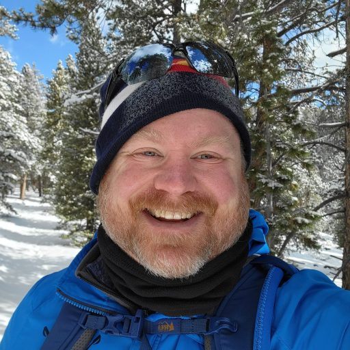 A picture of me with a wide smile standing on a snow covered trail surrounded by pine trees.  The Mental Health Benefits of Hiking visible on the smile on my face.