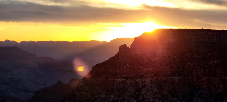 The sun as giant orange ball over the Grand canyon.