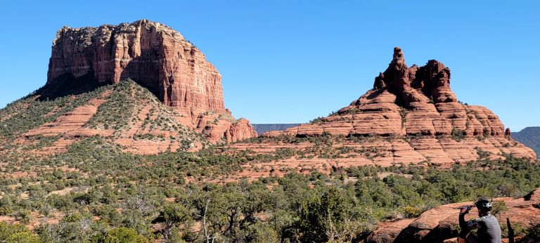 Two separate large Red Rock formations  in the background with green trees and red rock dispersed throughout the foreground from the Yavapai Vista Trail