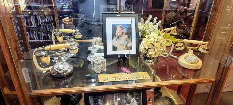 A display case with a photo of Betty Grable and some antique phones used in photos at El Rancho.