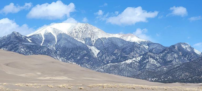 A giant snow packed mountain peak with a smaller dune in the foreground at the Great Sand Dune National Park.