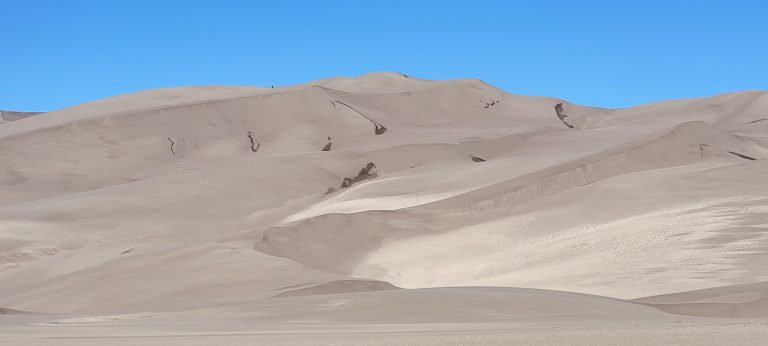 A view up to High Dune at the Great Sand Dune National Park.  The dunes almost look like a series of waves on an ocean of sand with dips and peaks.