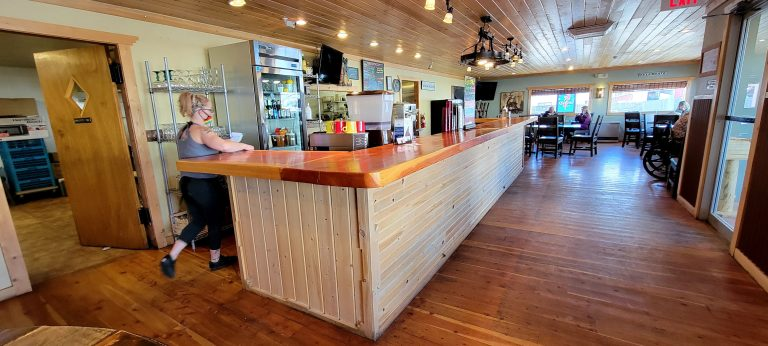The sleek lines of Lu's Main Street Café main dining area.  Wood flooring and a wood paneled bar give the restaurant a sleek look.