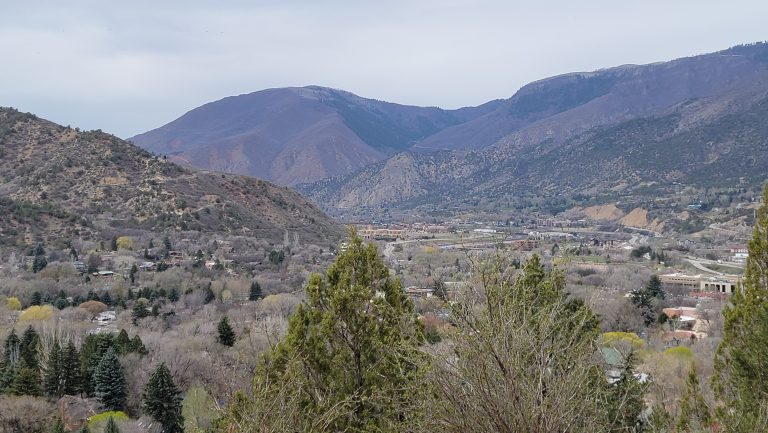 The view looking over Glenwood Springs from the trail on the way to Doc Holiday's Grave.  The view looks down towards the Glenwood Canyon with tall mountainsides on either side.