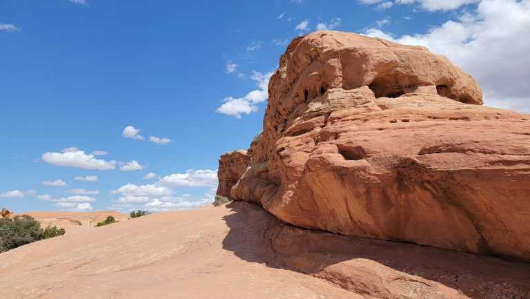 The top section has large rock formations next to the flat rock trails on the way to Delicate Arch. The rock formations are full of holes like a block of swiss cheese and tower over the base.