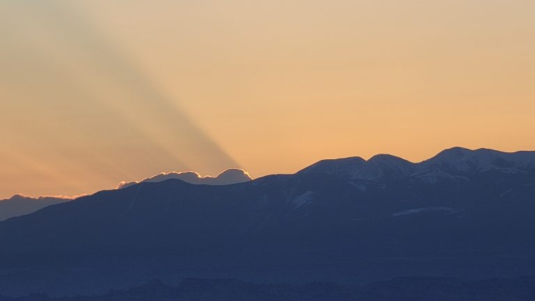 While waiting for sunrise at Mesa Arch the sun is still below the mountains but a series of rays are visible as streaks coming off a cloud that sits just above the mountains.