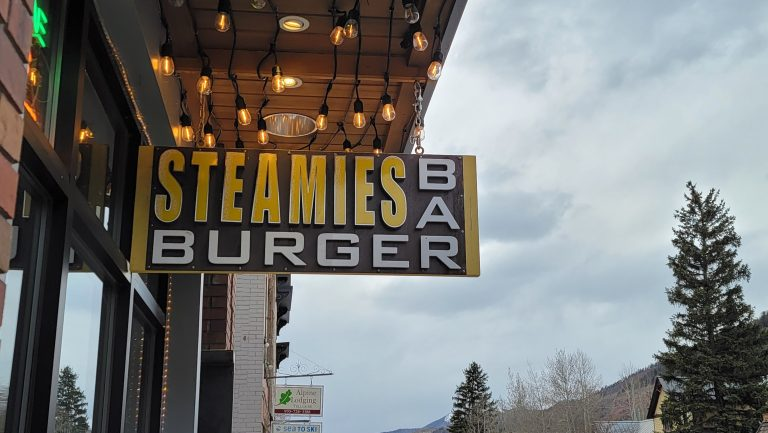 The sign for Steamies Burger Bar in Telluride is a rectangular wood sign with the word Steamies in yellow and burger bar framing it in white.