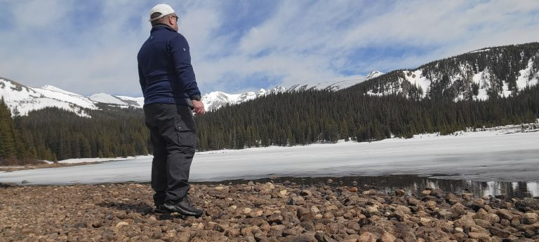 Me on a rocky beach in front of a frozen lake as part of my Kuhl Renegade Cargo Convertible Pant Review