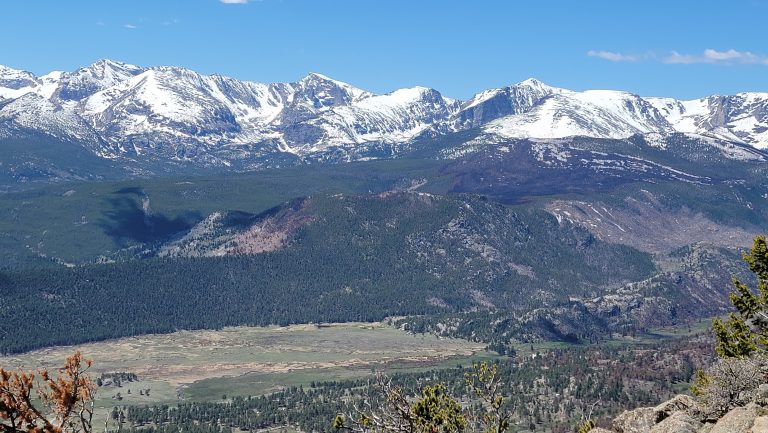 The view from the top of Deer Mountain.  The view has snow capped peaks at the top, tree covered hills in the middle and a large meadow at the bottom.