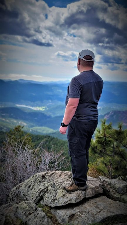 Me standing on the edge of a mountain top as part of my Kuhl Renegade Cargo Convertible Pant Review.