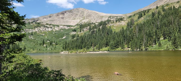 A small island sits in the middle of Kroenke lake which is nestled in among several peaks.