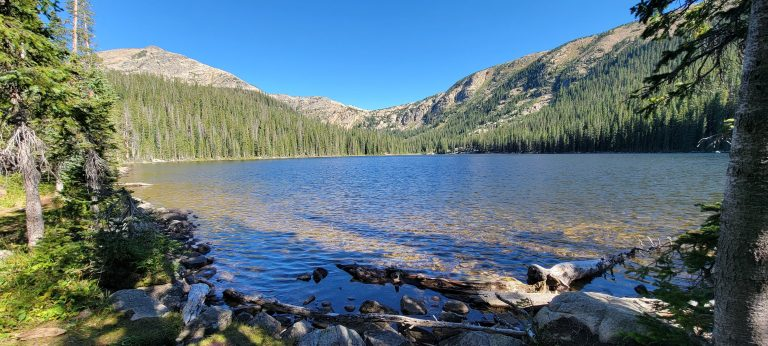 The view of Timberline Lake as you first approach it from the trail.  The trail is surrounded by mountains with rocky tops and pine trees about 2/3 of the way up.