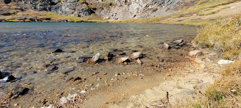 The rocky bank of Gibson Lake with clear water stretching out.