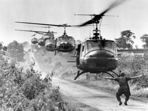 Um militar sinalizando uma fileira de helicópteros.