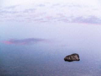 Rock in the lake with the sky's reflection. / Fujifilm X10