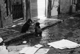 Children playing on the curb. Naples, Italy.