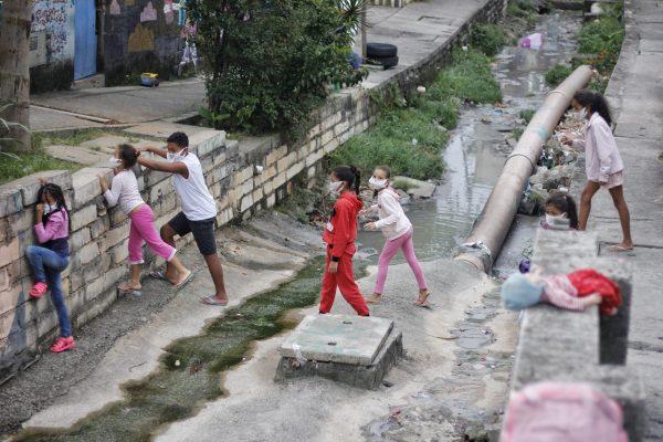 Crianças brincando com máscaras de sacola em periferia da cidade de São Paulo. Foto: Lucas Quinttino