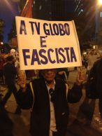"A man holds a sign calling the Globo media conglomerate fascist. The mammoth corporation (the largest media company in Latin America) supported military rule during the dictatorship (which they kinda, sorta issued a mea culpa for a few years ago), and is routinely accused by everyone on the left of political fascism, racism, misogyny, homophobia and sensationalism. Globo news outlets in turn accuse the protestors of being vandals, trouble makers, looters, and possible-terrorists. One side marches with signs, the other has newspapers, TV channels and radio stations. Guess who reaches a larger audience... When Globo covers protests, they often have to do so in disguise, for they are routinely chased away by protestors shouting insults and chanting ""Globo, fascista, racista, sensacionalista!"" [photo by Tucker Landesman]"