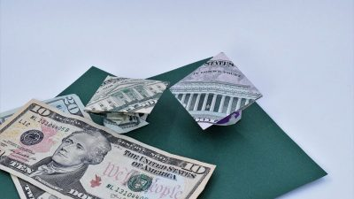 Dollar ORigami Graduation cap sitting on green paper with other dollar bills