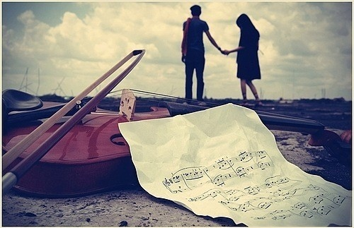 image of two persons in love with musical instrument in the background