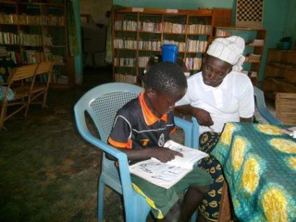 La gérante de Karaba encadre cet enfant en lecture