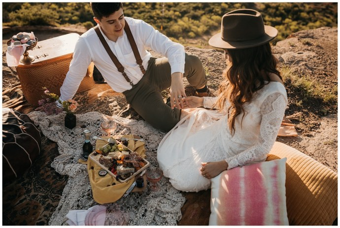 bride wearing lace gown and brimmed brown hat and groom wearing green pants, boots and suspenders enjoy a picnic on a desert cliff