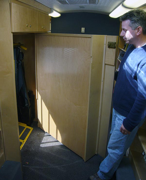 Man pulls open wall shelves to reveal a recess with a yellow lift inside