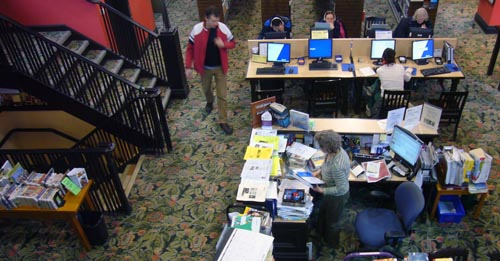 Overhead view shows librarians' desk, staircase off to the left, and long table of computer workstations all on top of green floral carpeting