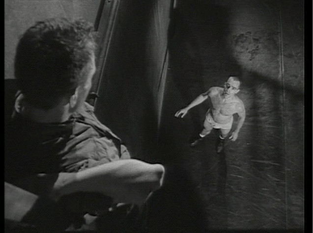 Man in underwear looks apprehensively up at another man perched far overhead by a wall