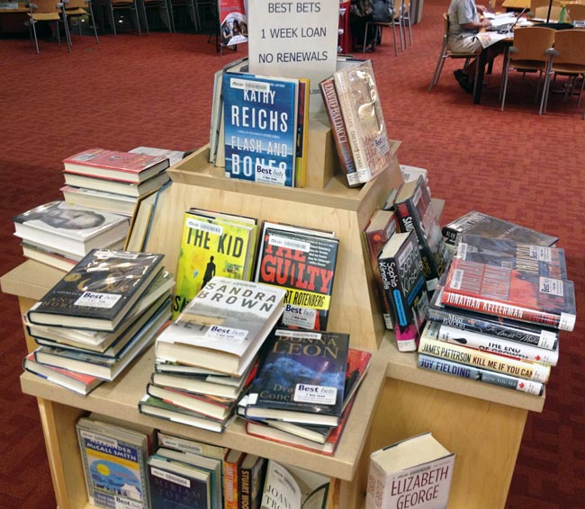 Books on Best Bets shelf piled face-up