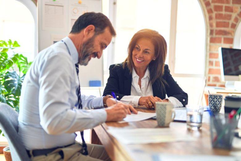 Két középkorú üzletember mosolyog boldogan és magabiztosan. Együtt dolgoznak mosollyal az arcukon laptopot használva az irodában.