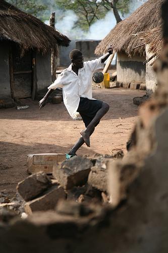 Um garoto joga futebol no campo de refugiados Oyam, em Uganda, em frente a uma cabana abandonada. Foto de E. Denholm, em dezembro de 2007, para a Agência da ONU para Refugiados (ACNUR/UNHCR)