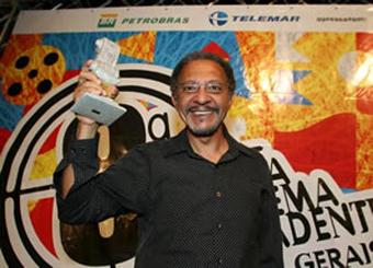 """Joel Zito recebendo a premiação de melhor filma na Mostra de Cinema Tiradentes, com o seu longa metragem """"Filhos do Vento. Foto: territoriopreto.blogspot.com"""
