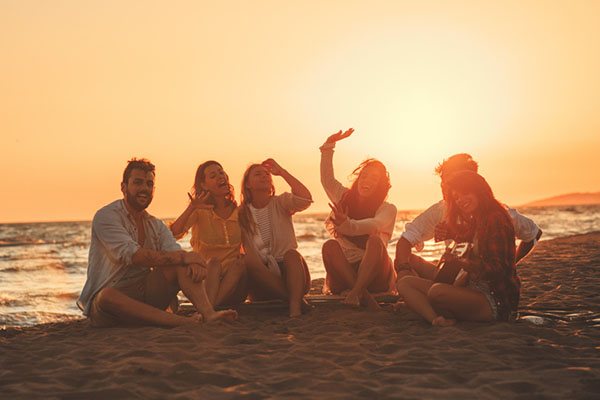 amigos sentados na praia no por do sol