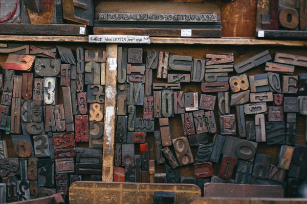 A drawer containing an assortment of wooden letters used in printing.