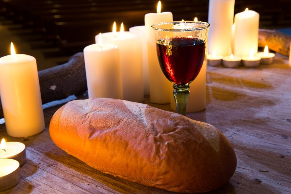 A loaf of bread sits beside a glass of wine on a wooden table, with several lit white candles in the background.