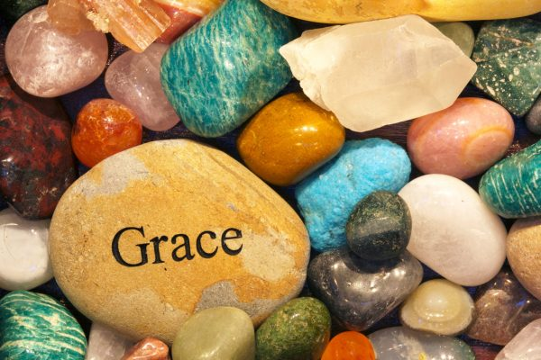 """A collection of stones of various shapes, sizes, and colors. A large golden yellow stone near the bottom lefthand corner reads, """"Grace""""."""