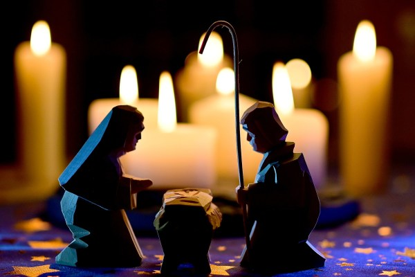 A Nativity scene in which the wooden carved figures of Mary, Joseph, and Jesus in the manger sit on a starry tablecloth, with lit candles of various different sizes in the background.