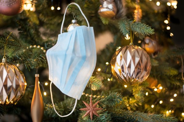 A blue disposable face mask hangs by an earloop on a Christmas tree, alongside golden ornaments and garlands.